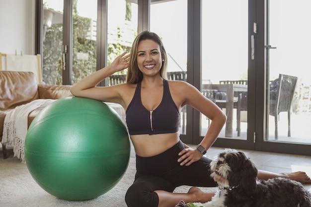 Retrato de uma linda mulher brasileira em roupas esportivas com bola de fitness e seu cachorro de estimação, exercícios em casa, conceito de aula de fitness online