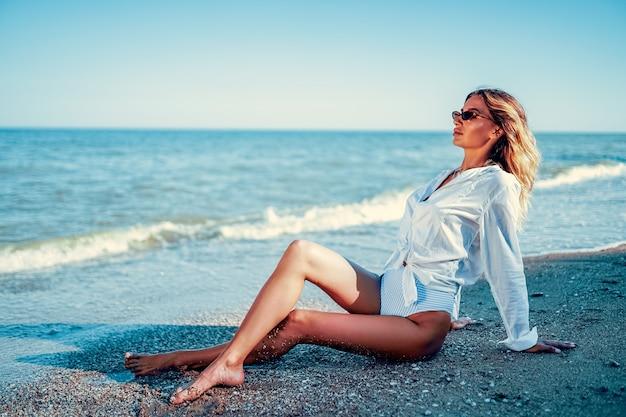Retrato de uma linda mulher bronzeada caucasiana sexy em óculos de sol com cabelos longos em traje de banho deitado na praia de verão