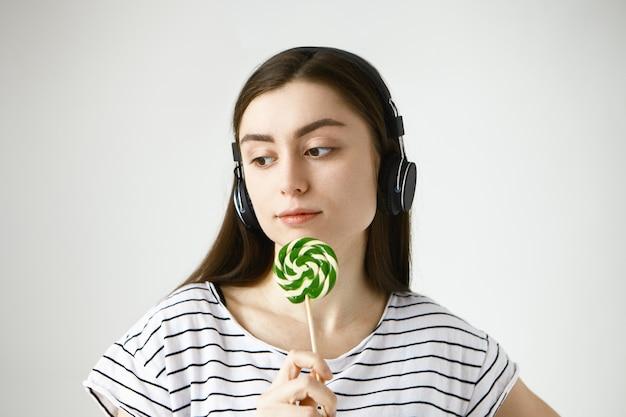 Retrato de uma linda mulher calma e sorridente, vestindo camiseta listrada e fone de ouvido sem fio, curtindo suas músicas favoritas online e lambendo pirulito