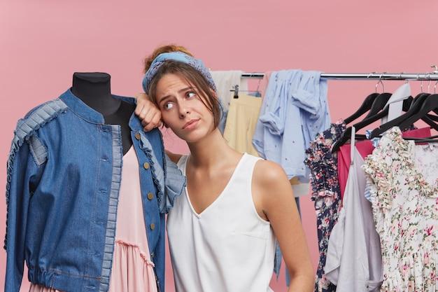 Retrato de uma linda mulher cansada, apoiando-se no manequim em pé com boutigue, estar exausto, experimentando roupas, tendo dúvidas sobre o que comprar. comprador do sexo feminino infeliz na loja de roupas, sentindo o tédio
