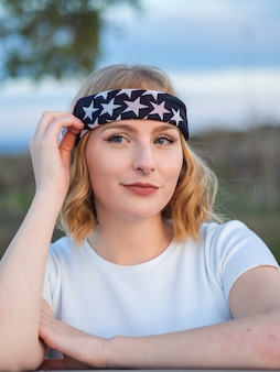 Retrato de uma linda mulher caucasiana com um piercing no nariz e uma bandana da moda em um parque