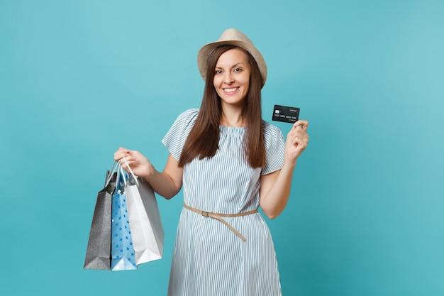 Retrato de uma linda mulher caucasiana com vestido de verão, chapéu de palha segurando sacolas de pacotes com compras após as compras, cartão de crédito do banco isolado em fundo azul pastel. copie o espaço para anúncio.