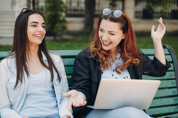 Retrato de uma linda mulher caucasiana dois sentado no banco, rindo, segurando um laptop nas pernas.
