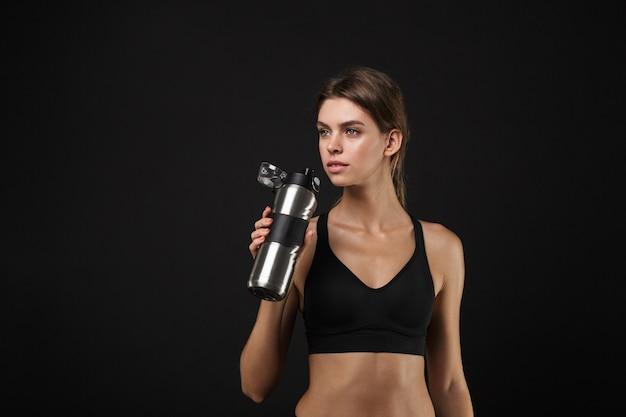Retrato de uma linda mulher caucasiana em roupas esportivas, bebendo água da garrafa durante um treino no ginásio isolado sobre o fundo preto