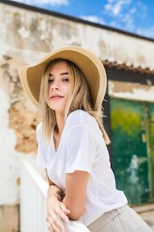Retrato de uma linda mulher caucasiana no terraço de verão com um sorriso no chapéu de verão