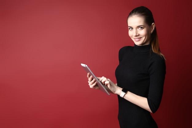 Retrato de uma linda mulher caucasiana sorridente em um vestido preto usando um tablet em um fundo vermelho