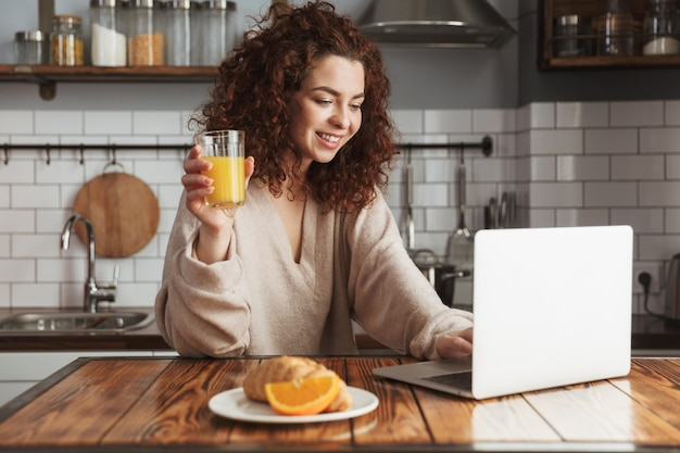 Retrato de uma linda mulher caucasiana usando laptop na mesa no interior da cozinha, enquanto toma o café da manhã em casa