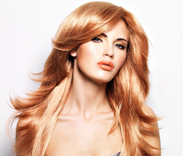 Retrato de uma linda mulher com cabelo longo liso vermelho e maquiagem glamorosa