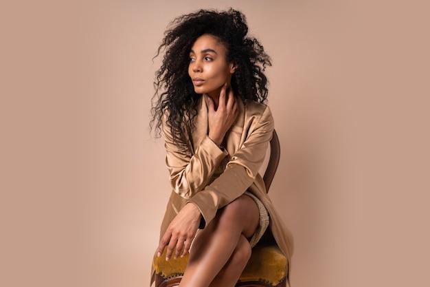 Retrato de uma linda mulher com cabelo ondulado perfeito em uma jaqueta dourada brilhante