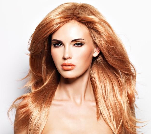 Retrato de uma linda mulher com cabelo vermelho longo e reto e maquiagem de glamour. modelo sobre parede branca