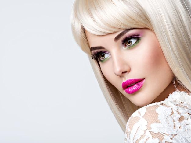 Retrato de uma linda mulher com cabelos lisos brancos e maquiagem nos olhos cor de rosa. rosto de uma modelo com batom rosa. menina bonita posando.