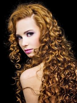 Retrato de uma linda mulher com cabelos longos cachos de beleza com maquiagem rosa brilhante de moda de olhos e lábios.