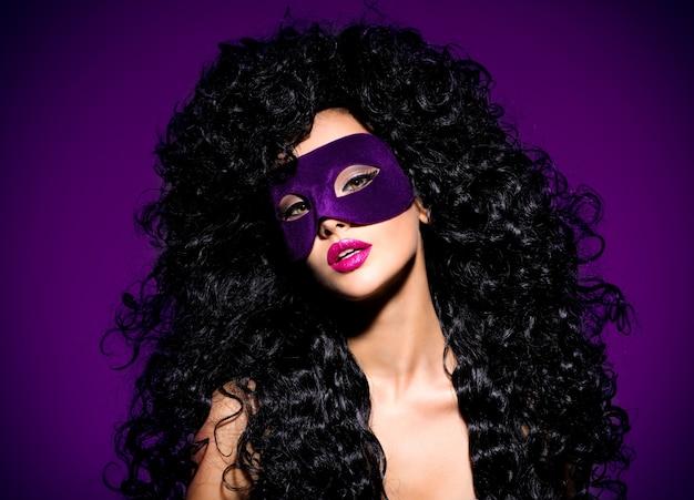 Retrato de uma linda mulher com cabelos pretos e máscara de teatro violeta no rosto. unhas roxas.