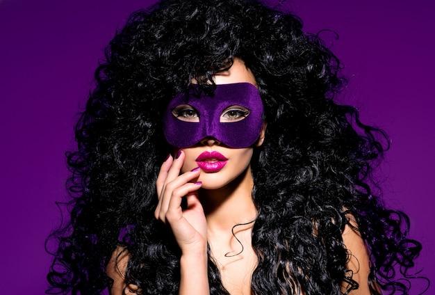 Retrato de uma linda mulher com cabelos pretos e máscara de teatro violeta no rosto.