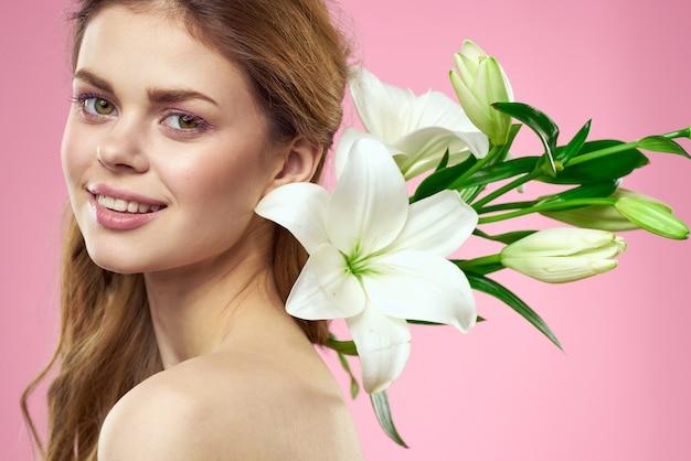 Retrato de uma linda mulher com flores brancas nas mãos em um fundo rosa.