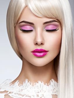 Retrato de uma linda mulher com maquiagem rosa e cabelos lisos brancos. rosto de uma modelo com batom rosa.