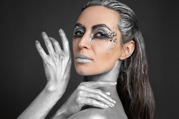 Retrato de uma linda mulher com tinta prateada na pele e no cabelo.