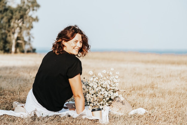 Retrato de uma linda mulher com um buquê de flores descansando sobre um tapete no campo