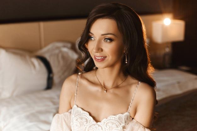 Retrato de uma linda mulher com um penteado de casamento e joias caras com diamantes. menina modelo morena com maquiagem de noiva e brincos de luxo