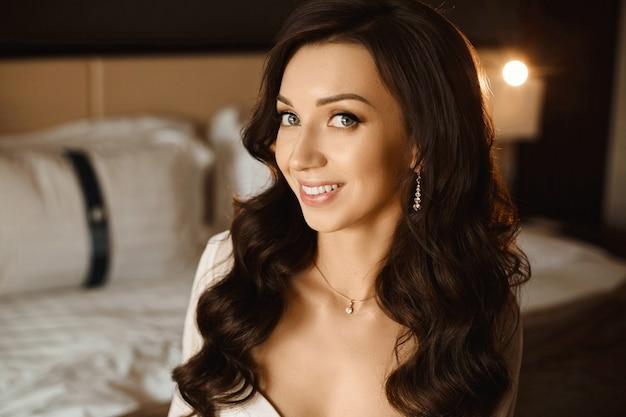 Retrato de uma linda mulher com um penteado de casamento e joias caras com diamantes