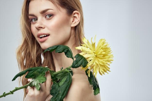 Retrato de uma linda mulher com uma flor amarela sobre um fundo claro sorriso encantador modelo vermelho