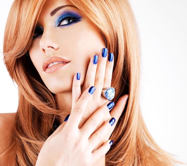Retrato de uma linda mulher com unhas azuis, maquiagem azul e longos cabelos vermelhos na parede branca