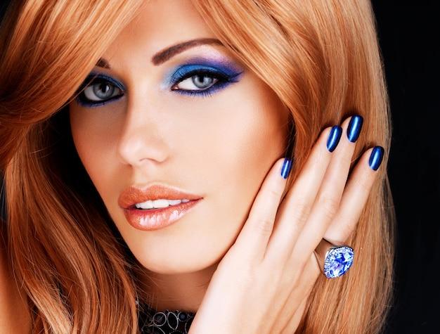 Retrato de uma linda mulher com unhas azuis, maquiagem azul e longos cabelos vermelhos na parede preta