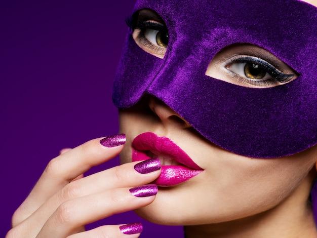 Retrato de uma linda mulher com unhas roxas e máscara de teatro violeta no rosto.