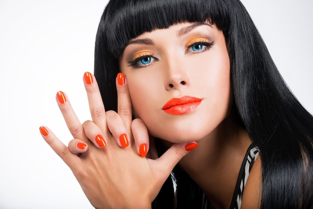 Retrato de uma linda mulher com unhas vermelhas e maquiagem glamorosa e longos cabelos negros