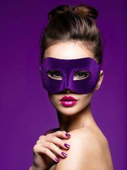 Retrato de uma linda mulher com unhas violetas e máscara de teatro no rosto.