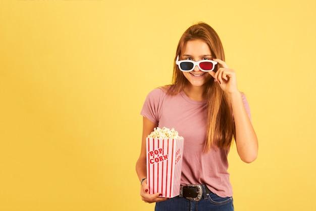 Retrato de uma linda mulher comendo pipoca e usando óculos 3d