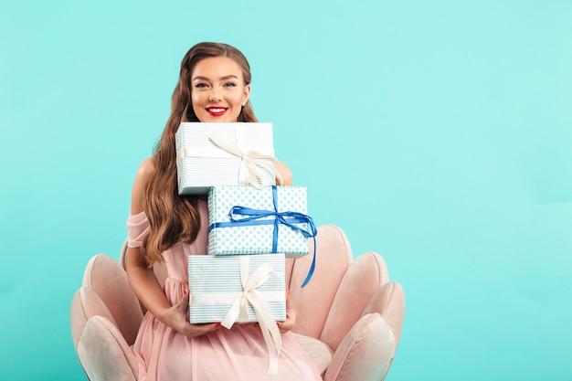 Retrato de uma linda mulher de 20 anos com longos cabelos castanhos segurando várias caixas de presente enquanto está sentada na poltrona rosa, isolada sobre uma parede azul