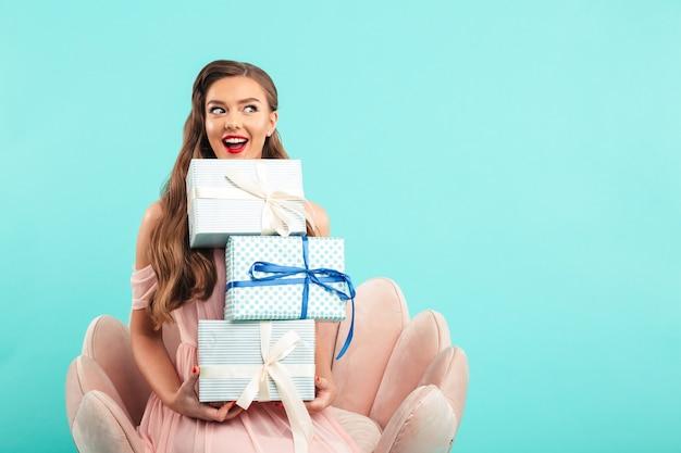 Retrato de uma linda mulher de 20 anos em um vestido rosa segurando várias caixas de presentes enquanto está sentado na poltrona, isolado sobre uma parede azul
