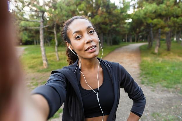 Retrato de uma linda mulher de 20 anos usando um agasalho esportivo preto e fones de ouvido, tirando uma foto de selfie no celular enquanto caminha pelo parque verde