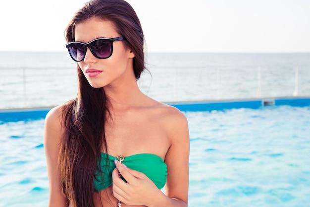 Retrato de uma linda mulher de biquíni e óculos escuros em pé com piscina na parede