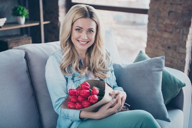 Retrato de uma linda mulher de cabelos ondulados sentado em um divã segurando flores vermelhas nas mãos