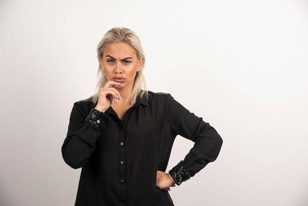 Retrato de uma linda mulher de camisa preta, posando em fundo branco. foto de alta qualidade