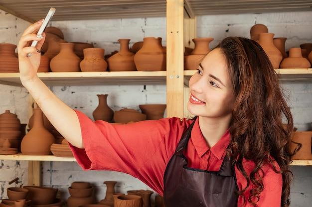 Retrato de uma linda mulher de ceramista fazendo selfie no telefone. uma mulher trabalha com argila em uma roda de oleiro e se fotografa em uma oficina de cerâmica.