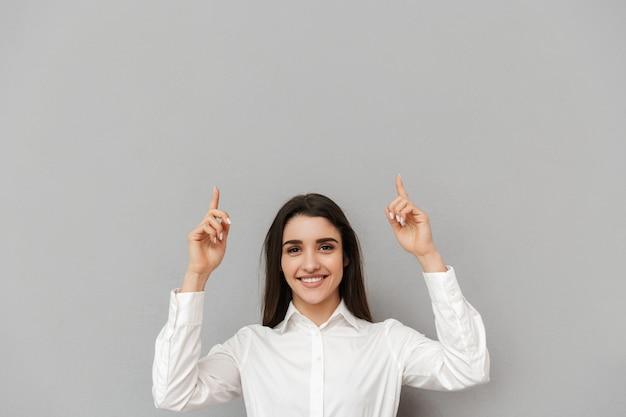 Retrato de uma linda mulher de escritório com longos cabelos castanhos em uma camisa branca apontando os dedos para cima na copyspace com um sorriso, isolado sobre uma parede cinza
