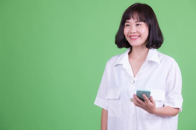 Retrato de uma linda mulher de negócios asiática com cabelo curto contra chroma key ou parede verde