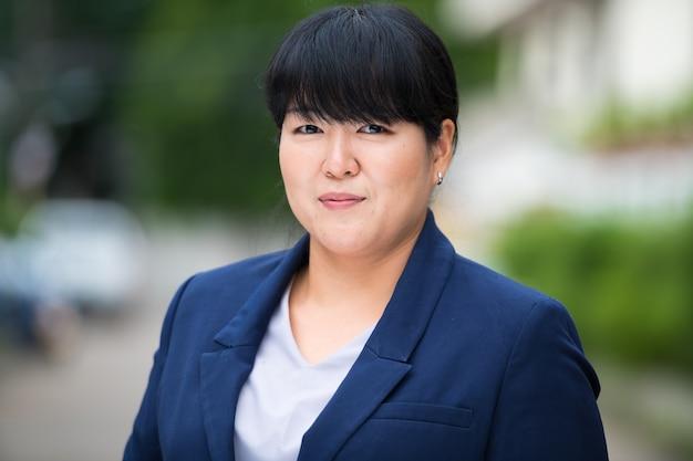Retrato de uma linda mulher de negócios asiática com excesso de peso na rua ao ar livre