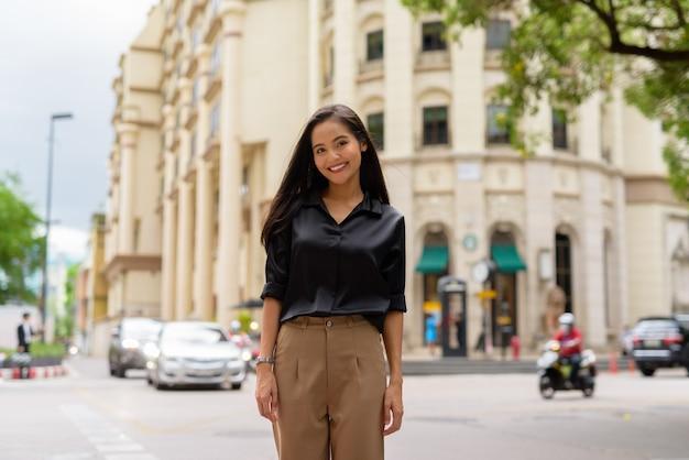 Retrato de uma linda mulher de negócios asiática sorrindo ao ar livre na rua da cidade enquanto caminha