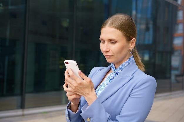 Retrato de uma linda mulher de negócios com uma jaqueta azul, falando ao telefone no contexto de um prédio de escritórios