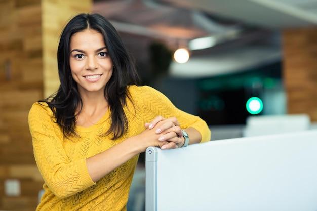 Retrato de uma linda mulher de negócios feliz em pé no escritório