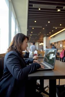 Retrato de uma linda mulher de negócios japonesa madura trabalhando dentro de um restaurante no shopping