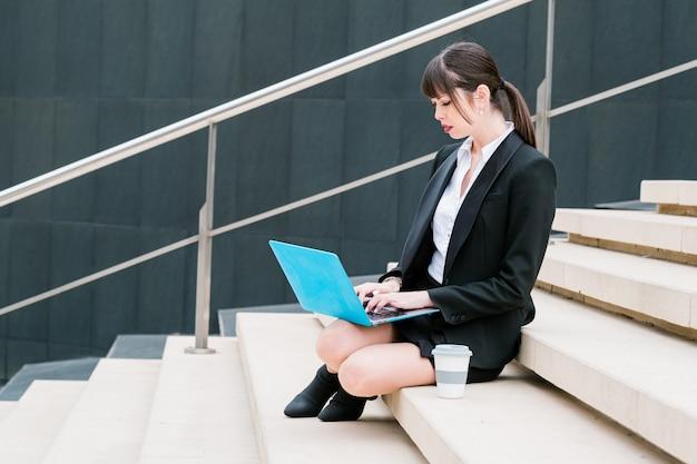 Retrato de uma linda mulher de negócios usando laptop em degraus na rua da cidade