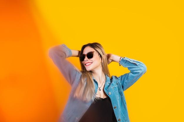 Retrato de uma linda mulher de óculos escuros e fundo amarelo.