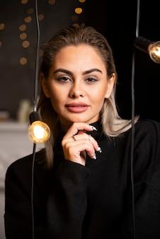 Retrato de uma linda mulher de suéter preto em pé e posando