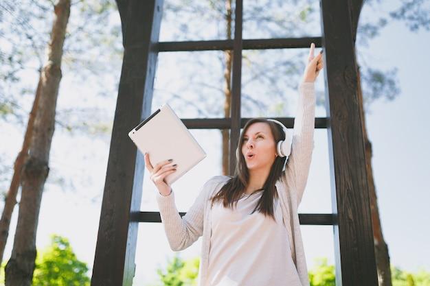Retrato de uma linda mulher divertida, vestindo roupas leves casuais. menina bonita, segurando o computador tablet pc, ouvindo música em fones de ouvido no parque da cidade, na rua ao ar livre na natureza da primavera. conceito de estilo de vida.