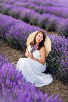 Retrato de uma linda mulher em lavanda. uma garota com um vestido de verão branco e um chapéu no verão na natureza.